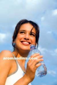 Young woman drinking water outdoors.