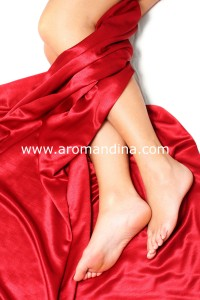 Pretty woman's legs with luxury red silk sheet